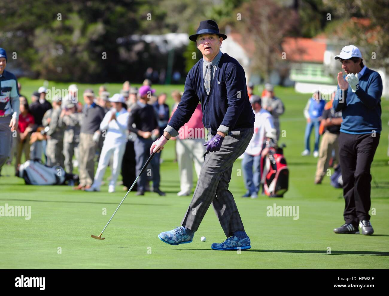 Actor and comedian Bill Murray wearing a matching navy blue sweater and hat watches his putt during the AT&T - Stock Image