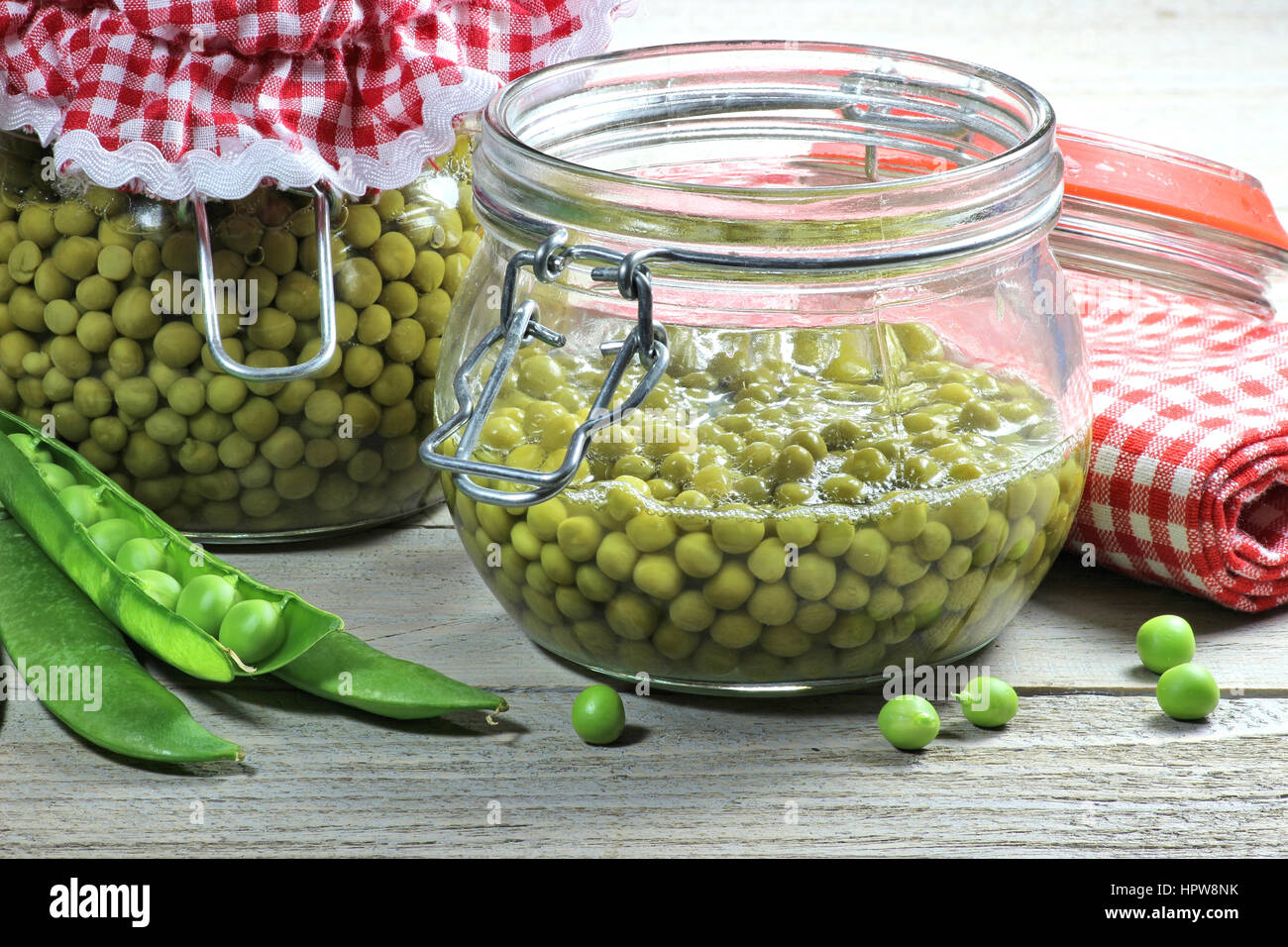 home canned peas on wooden table - Stock Image