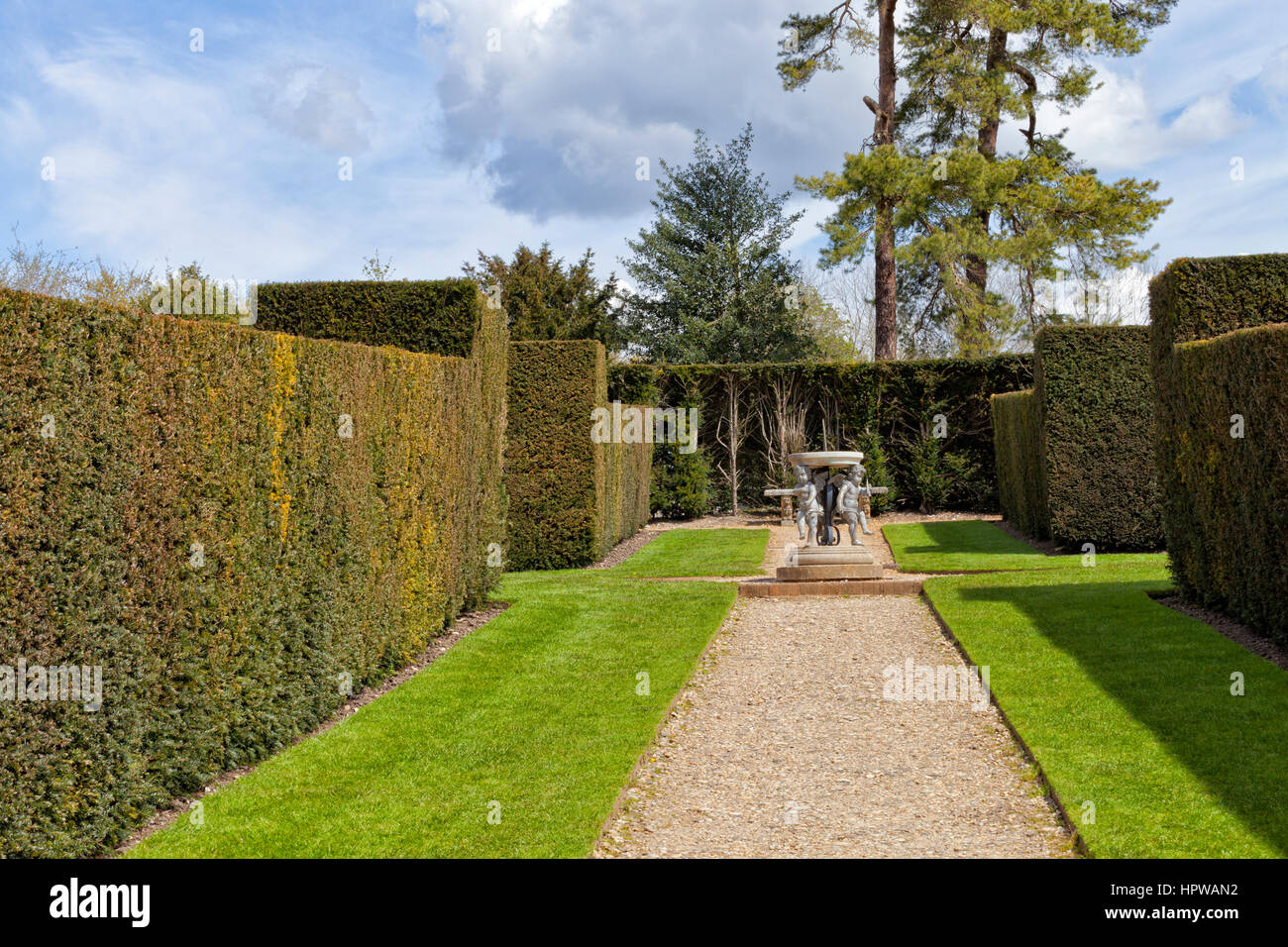 Garden with a path leading to a stone sundial ornament between tall hedge walls - Stock Image