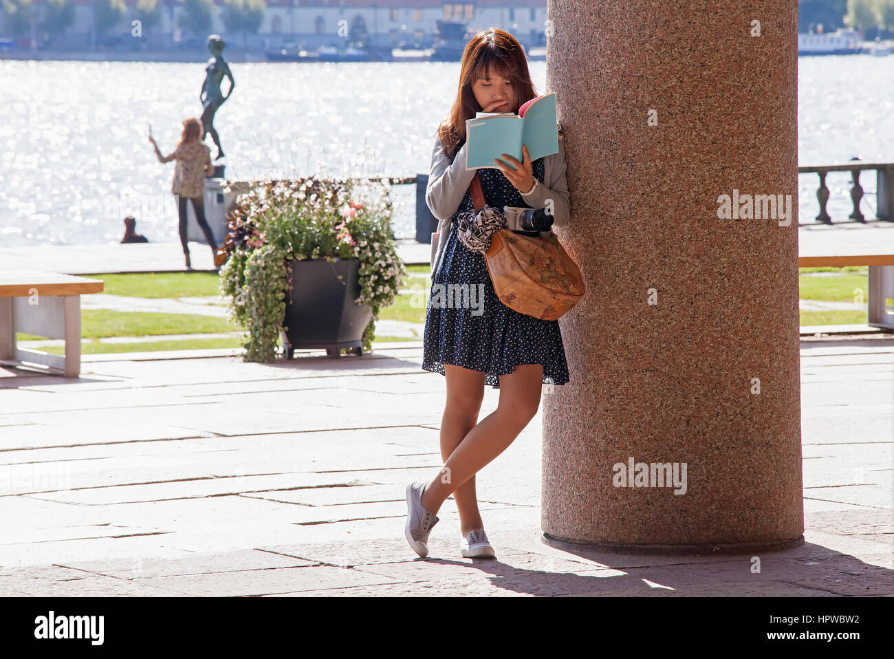 Asian woman resting on a pillar absorbed in reading. - Stock Image