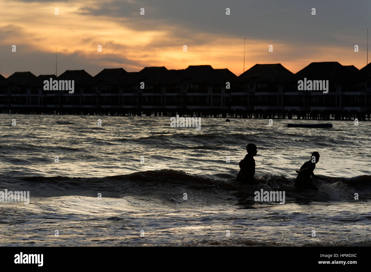 children playing at beach in Bagan Lalang, west coast Malaysia - Stock Image