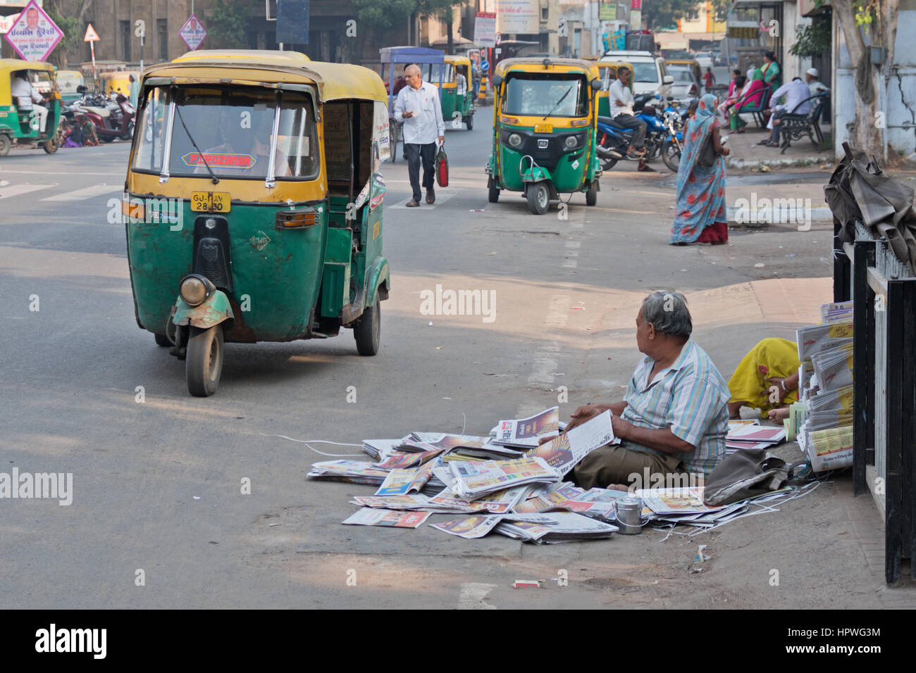 An unidentified newspaper seller with a pitch on a busy street in Ahmedabad, India, amidst the early morning traffic - Stock Image