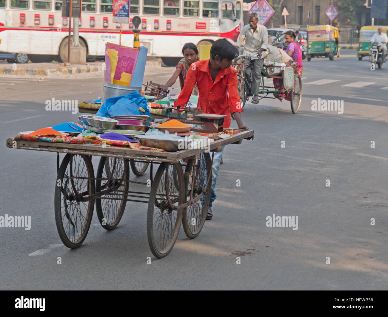 An unidentified trader wheeling a cart laden with dyes through the centre of Ahmedabad, India, to a local market - Stock Image