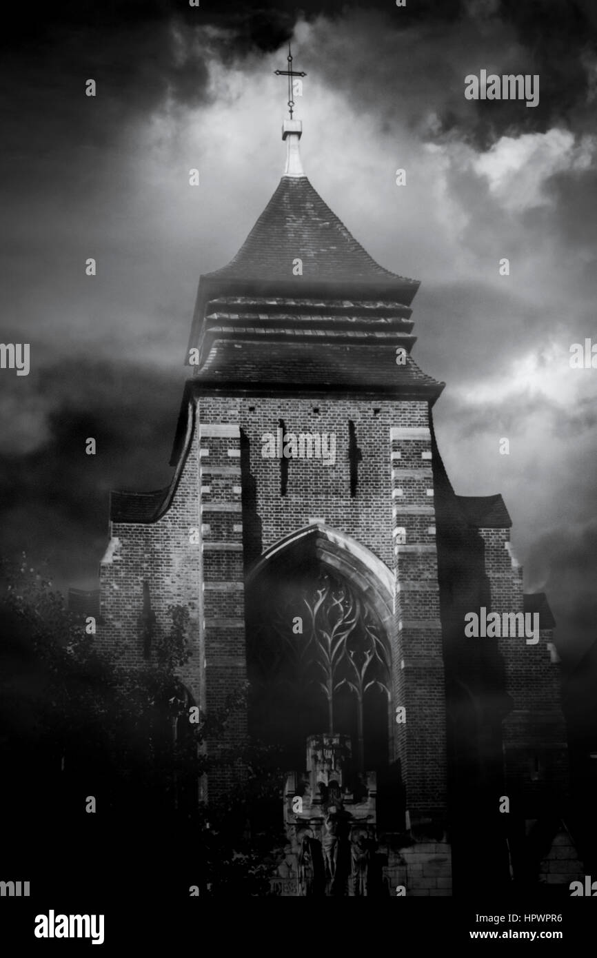Black and white image of a church tower looming from the mist against a cloudy moonlit night sky Stock Photo