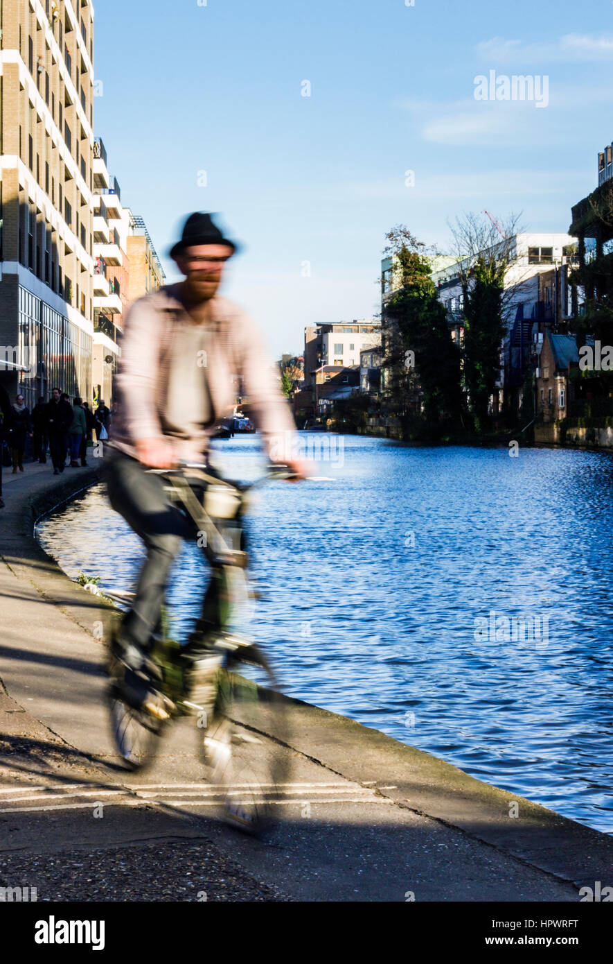 Bearded man wearing a hat and riding a bicycle along the towpath of Regent's Canal, London, UK, blurred with - Stock Image