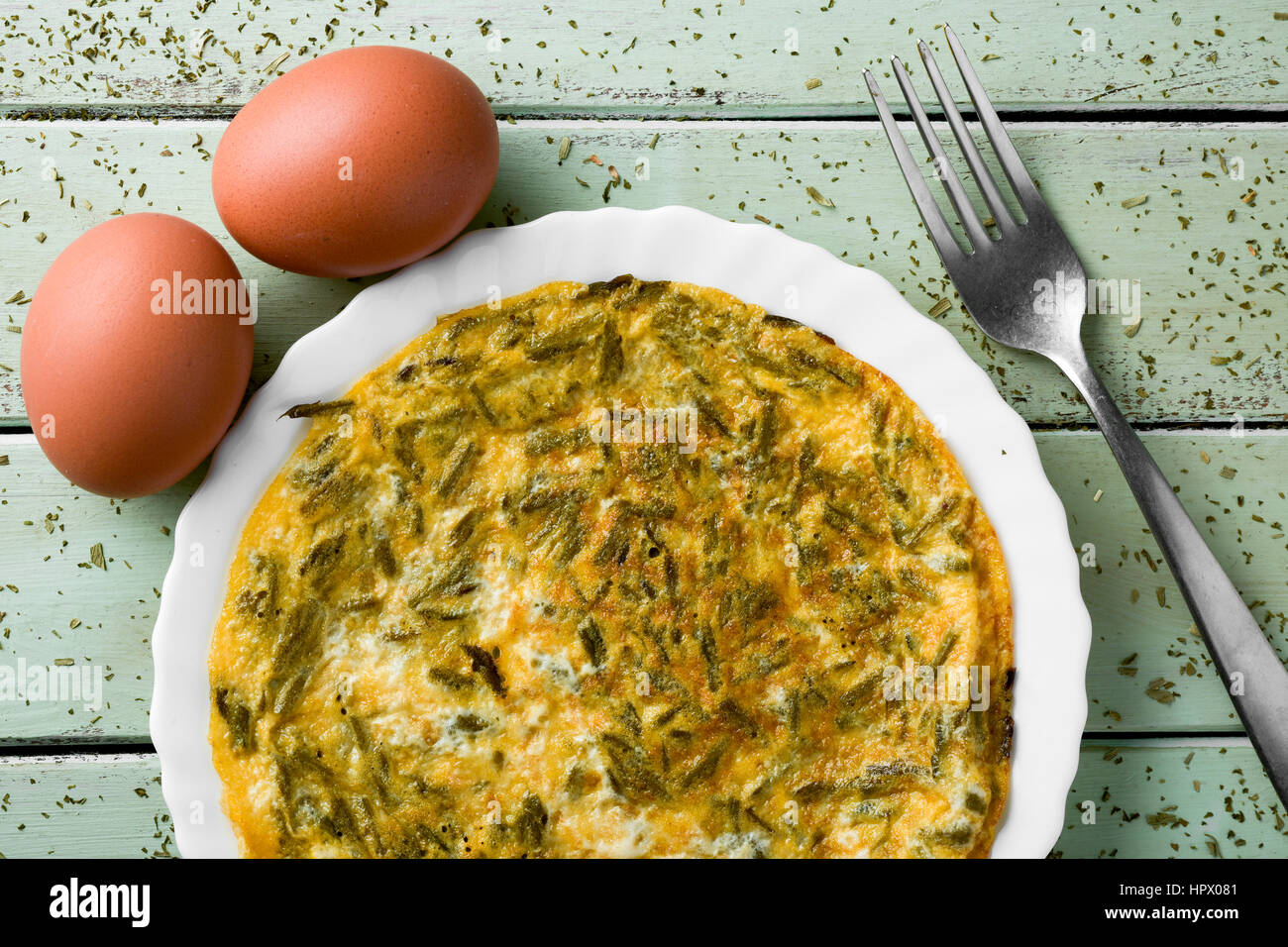 a spanish tortilla de esparragos, an omelet made with wild asparagus, and some eggs on a pale green rustic wooden - Stock Image