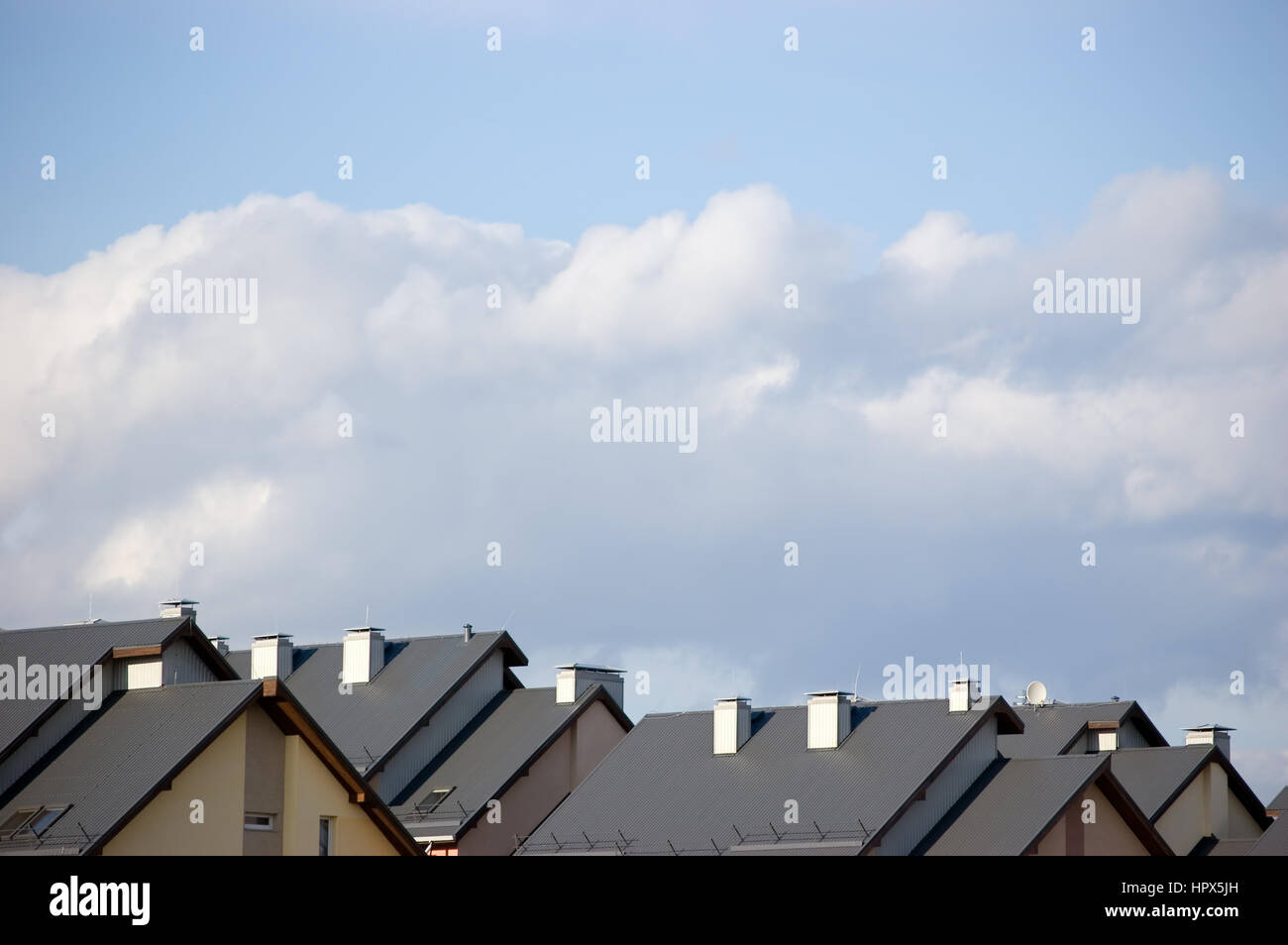 Row house roofs, condo houses rooftop panorama, bright summer clouds cloudscape, townhouse condos rooftops - Stock Image