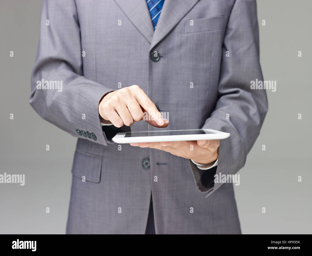 business person in suit using a tablet computer, gray background. - Stock Image