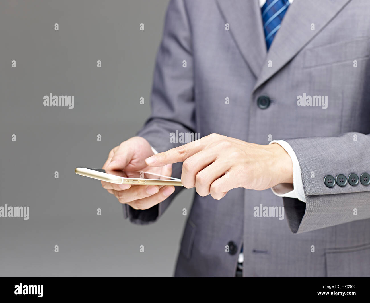 businessman using a mobile phone with finger pointing at the screen, gray background. - Stock Image