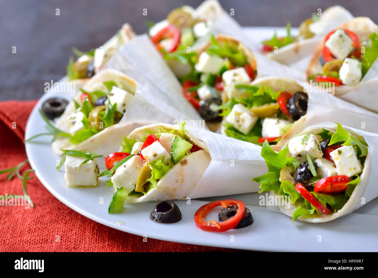 Mini tortillas stuffed with Greek farmers salad with feta cheese and olives, served in white paper bags Stock Photo
