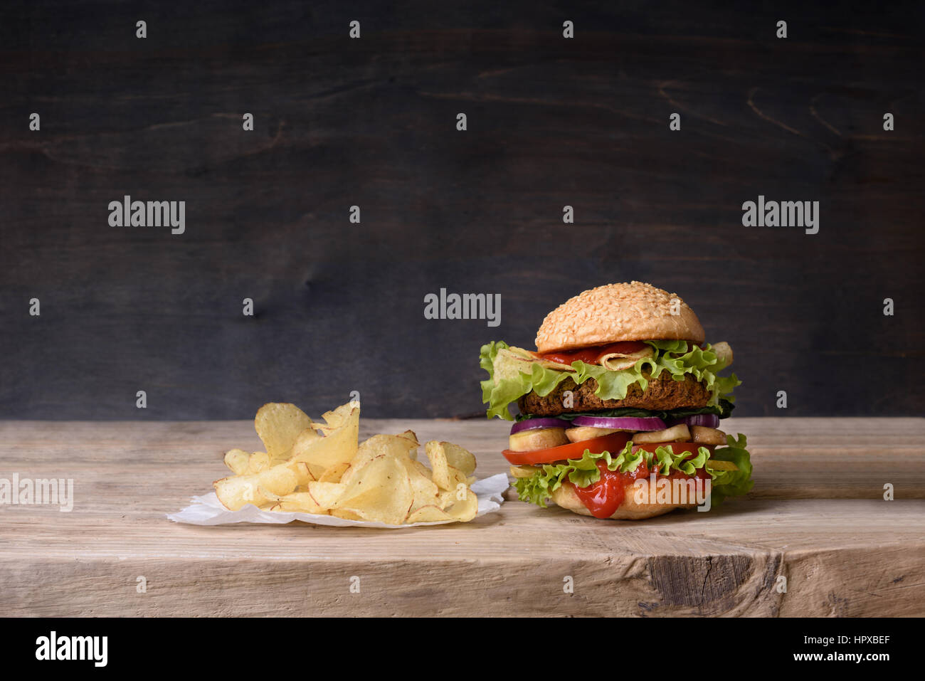 Delicious burger with beef, tomato, cheese, lettuce and potato chips on wooden counter. Copy space. - Stock Image
