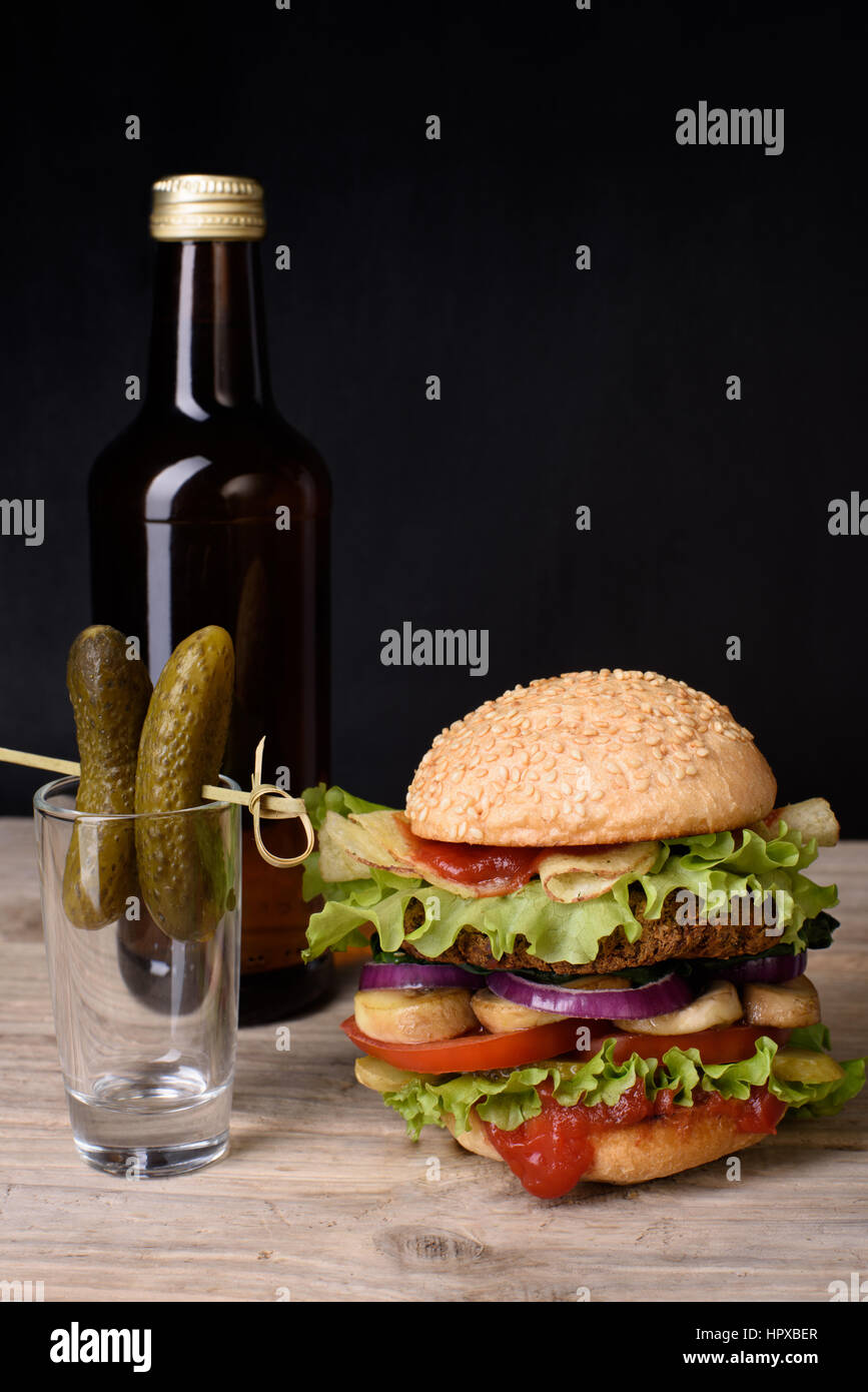 Grilled hamburger with bottle of bear and pickles on wooden table, dark background. Free text space. - Stock Image