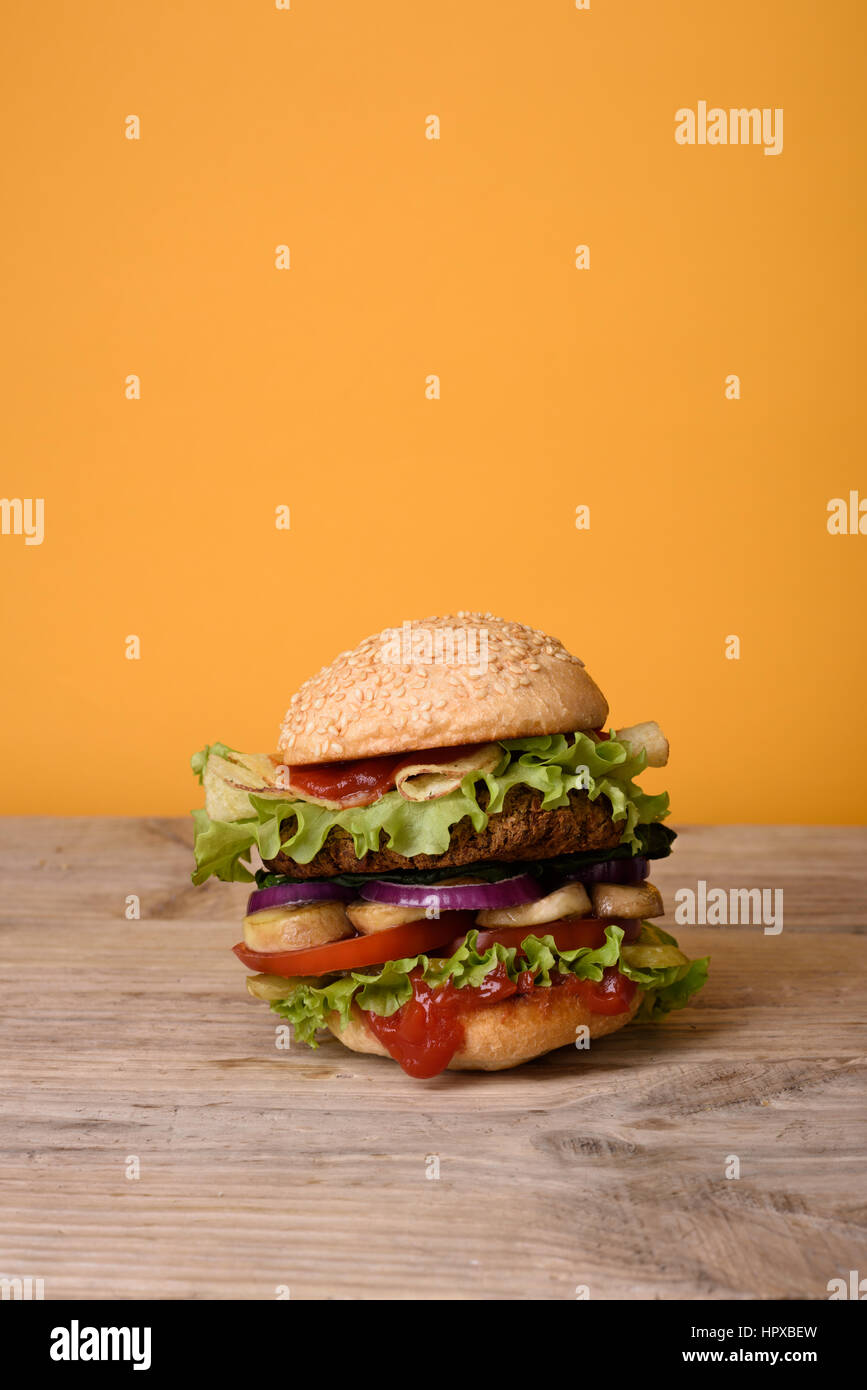 Grilled burger on rustic wooden table, yellow background. Free text space. - Stock Image