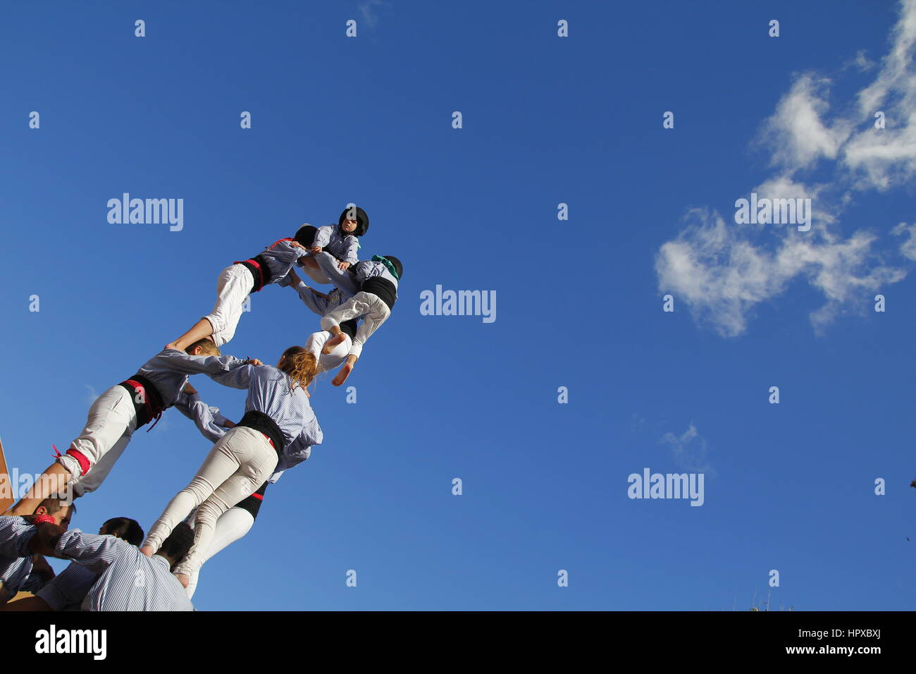 People making human towers, a traditional spectacle in Catalonia called 'castellers', with people climbing - Stock Image