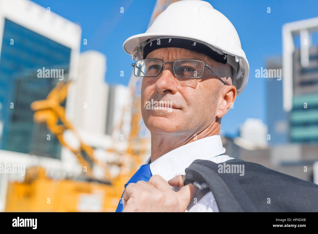 Confident construction engineer in hardhat and with jacket on shoulder Stock Photo
