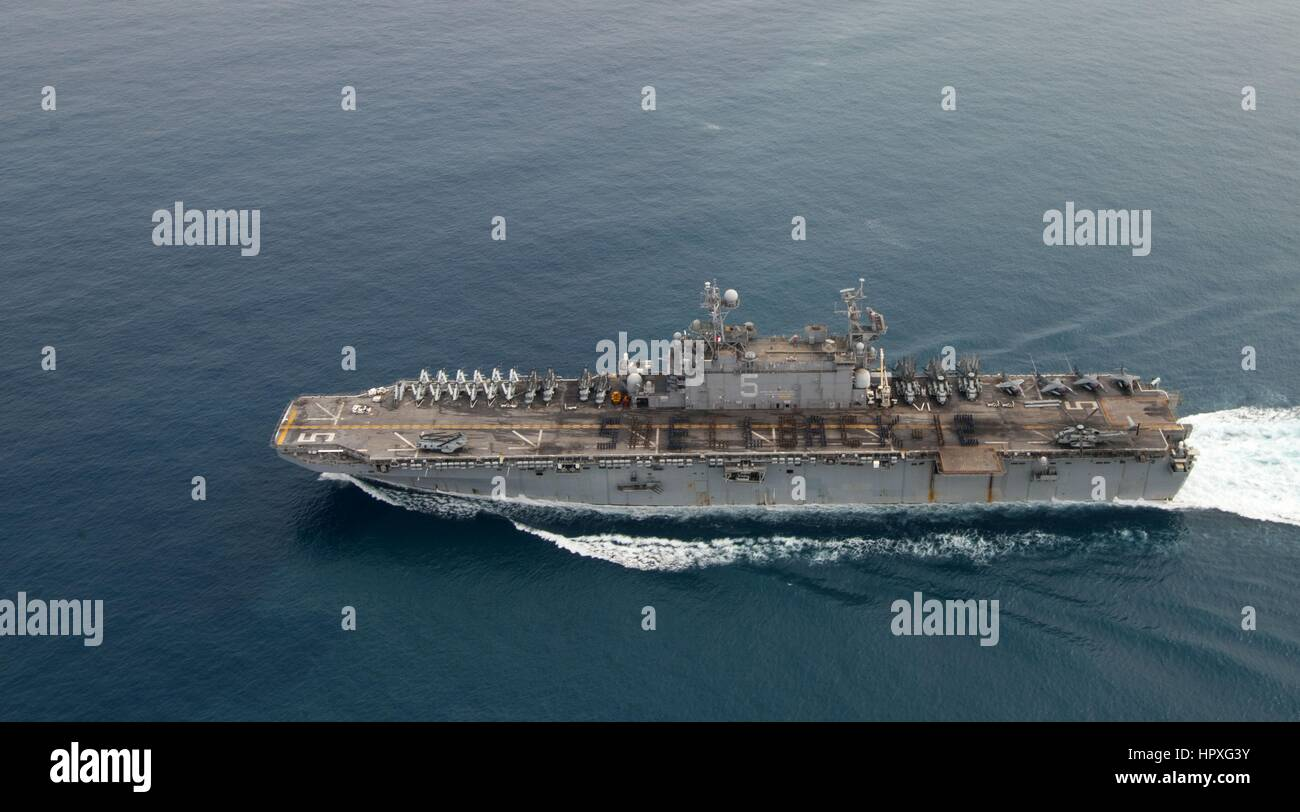 Sailors and Marines aboard amphibious assault ship USS Peleliu (LHA 5) stand in formation, spelling out SHELLBACK - Stock Image