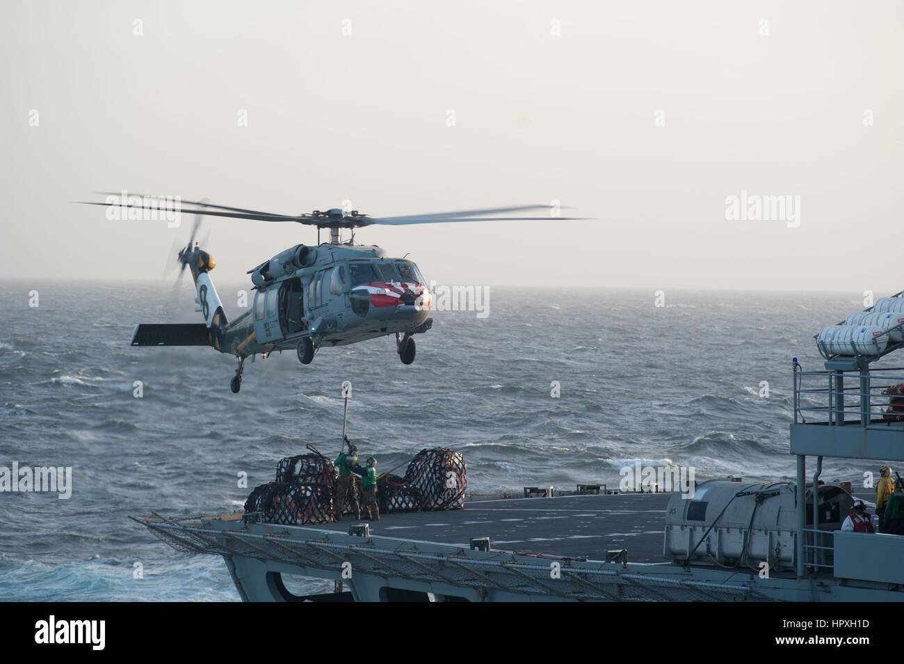 Military Sealift Command fast combat support ship USNS Bridge (T-AOE 10) and an MH-60S Sea Hawk helicopter during - Stock Image