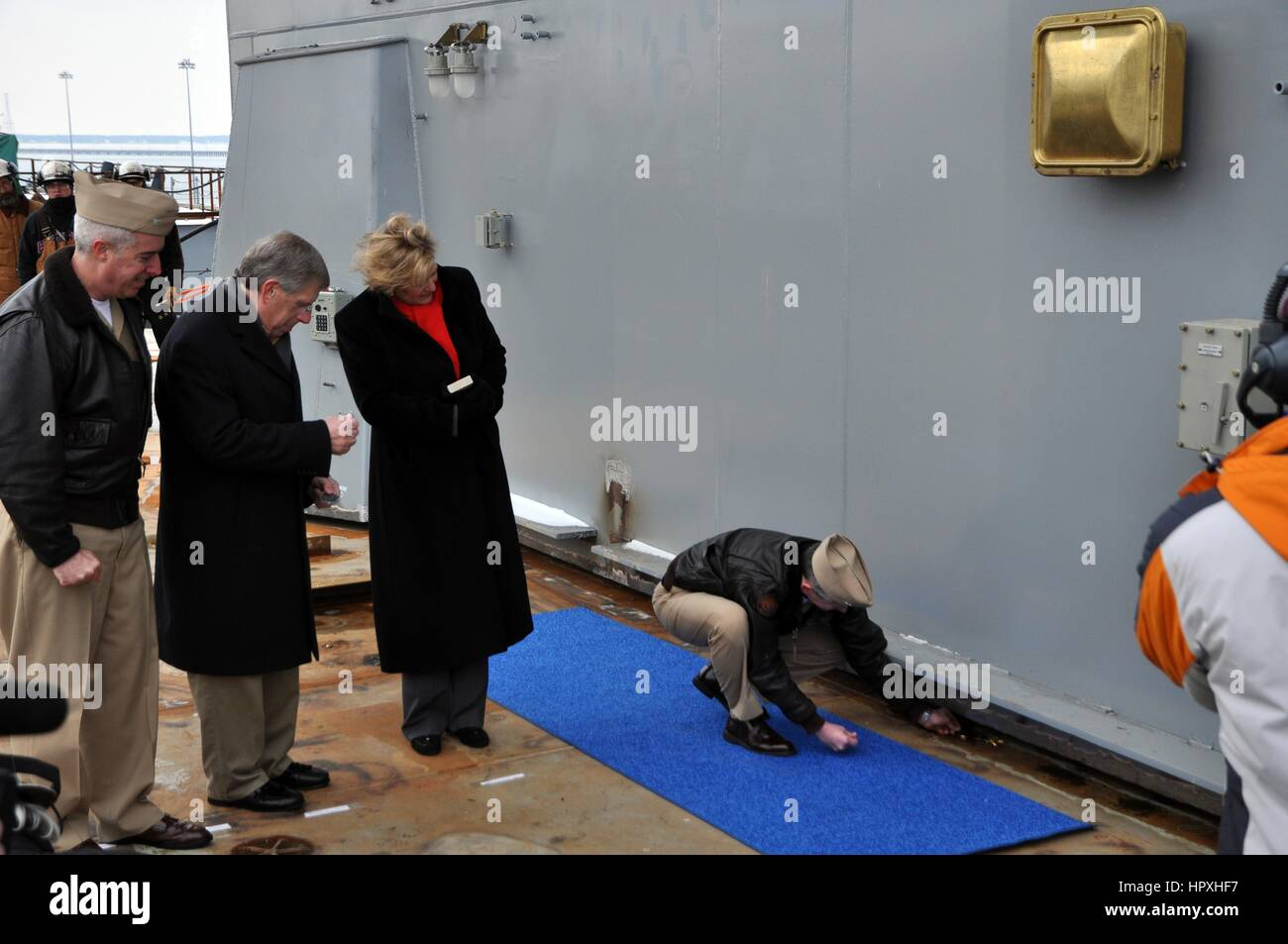 Admiral Ted N. Branch, commander of Naval Air Force Atlantic, places several coins under the island of the future - Stock Image