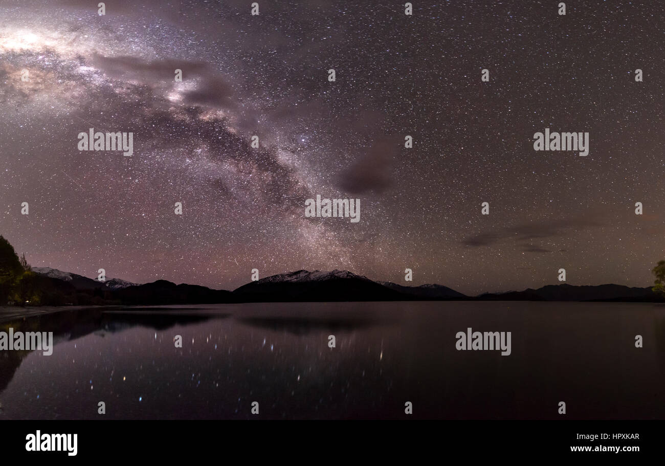 Night Scene, Wanaka lake with stars and Milky Way, stars mirroring in the water, Glendhu Bay, Otago, Southland, - Stock Image