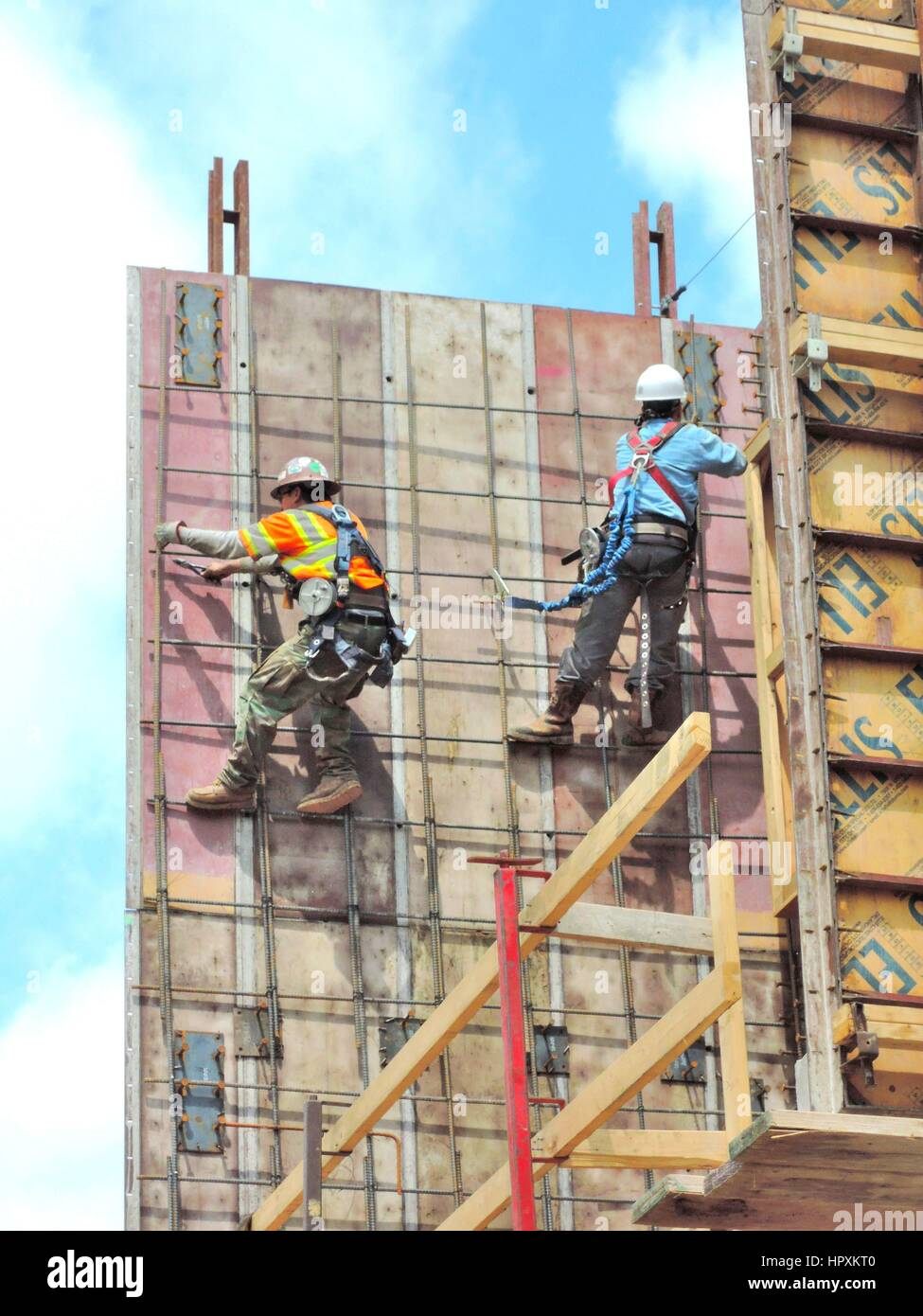 Construction Workers Working In Safety Harnesses Stock