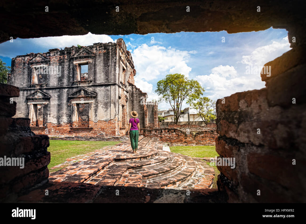 Woman in hat looking at ancient ruined Temple of city Lopburi, Thailand - Stock Image