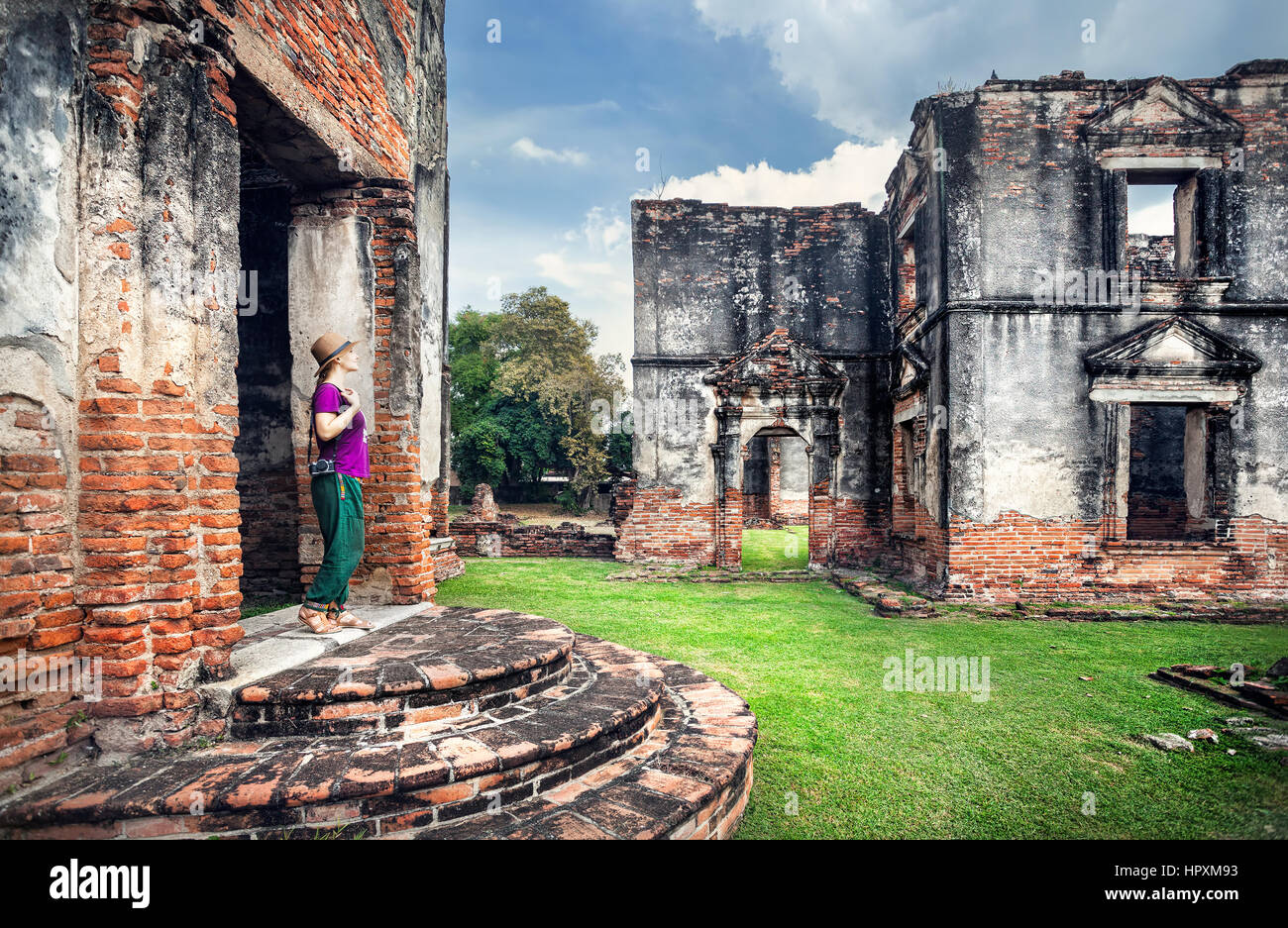 Woman tourist with photo camera looking at ancient ruined Temple of city Lopburi, Thailand - Stock Image