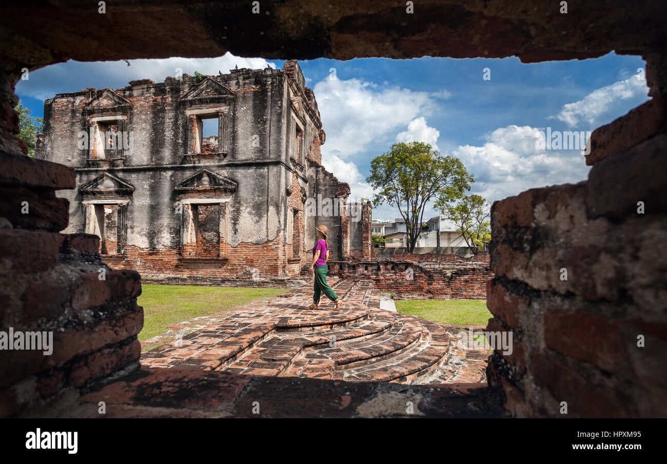 Woman tourist in hat walking at ancient ruined Temple of city Lopburi, Thailand - Stock Image