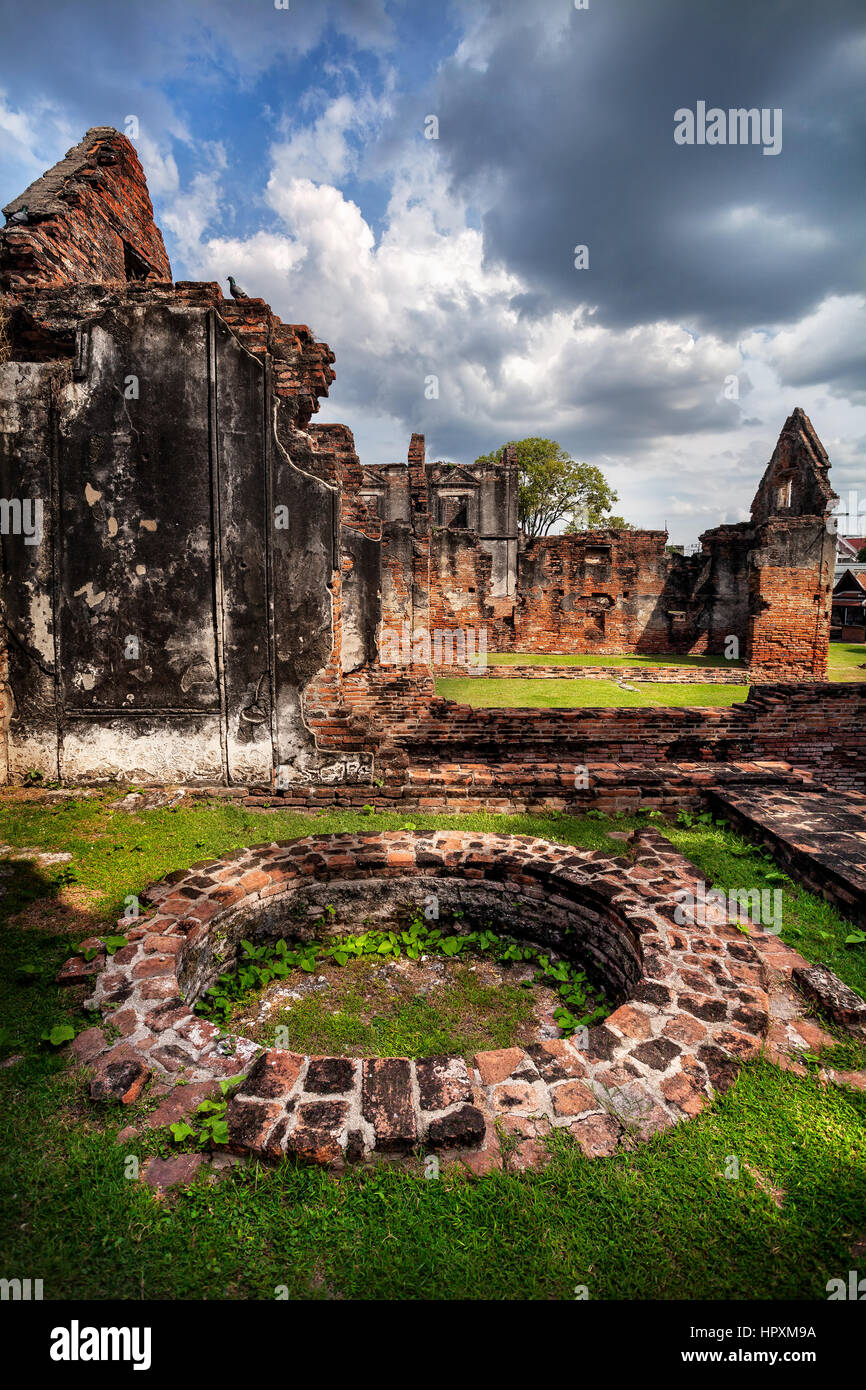 Ancient ruined walls and well of Temple in Lopburi at sunset sky, Thailand - Stock Image