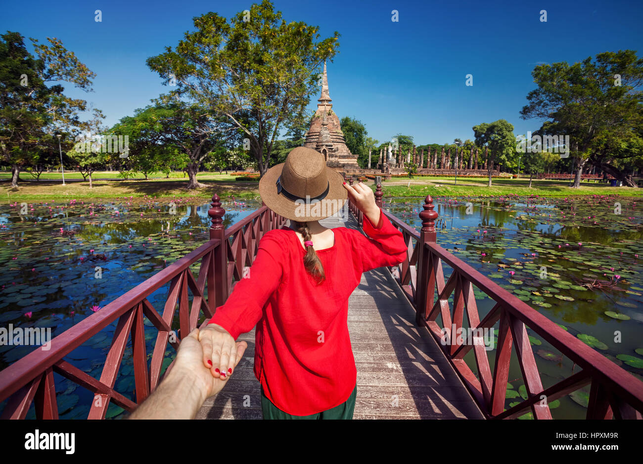 Tourist Woman in red shirt holding her husband by hand and going to ancient stupa in Sukhohai Historical Park, Thailand - Stock Image