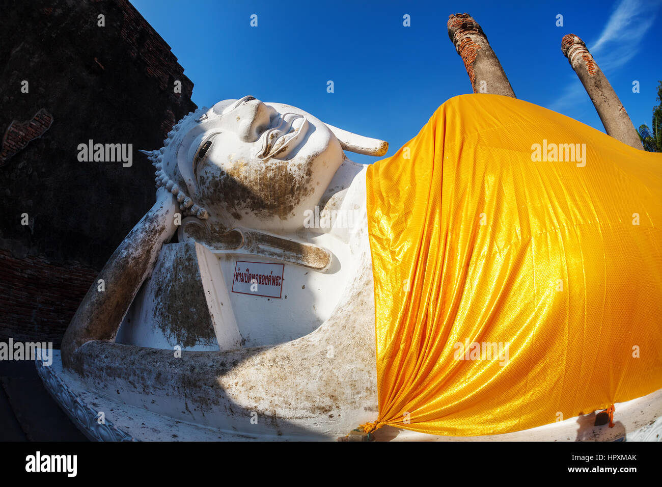 Big Lying Buddha statue with yellow robe in Wat Yai Chai Mongkol monastery in Ayuttaya, Thailand - Stock Image