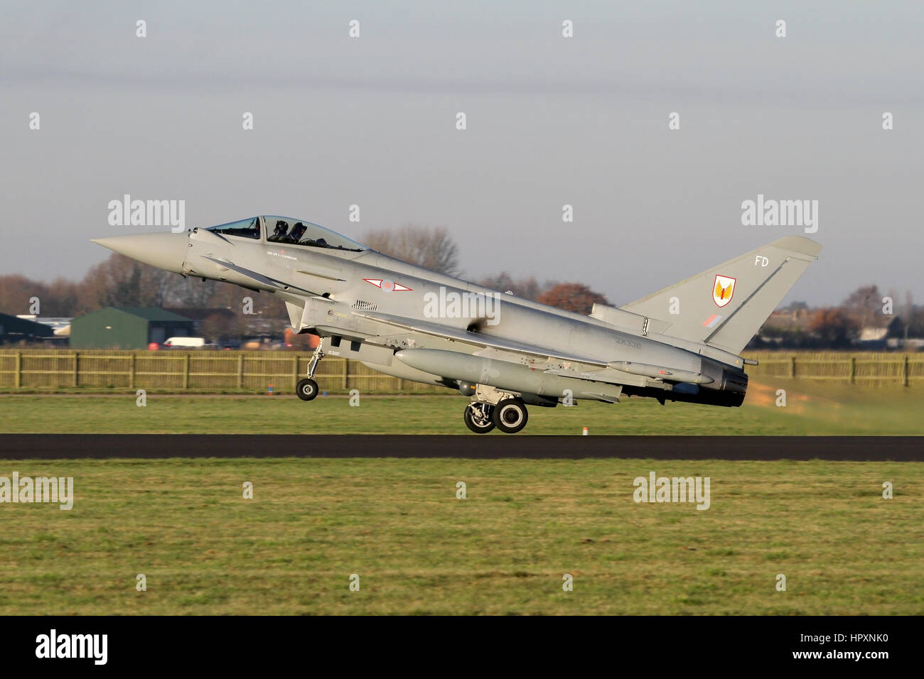 A rare use of reheat/afterburner from a RAF Typhoon as it rotates of the runway at RAF Coningsby in the low light. - Stock Image