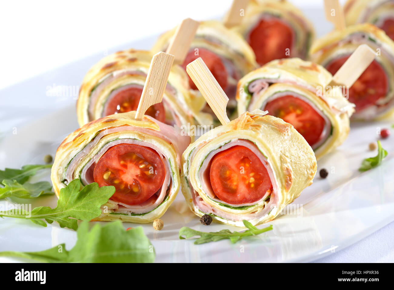 Delicious finger food: Rolls of thin pancakes (crepes) with ham, cream cheese, rocket salad and cherry tomatoes - Stock Image