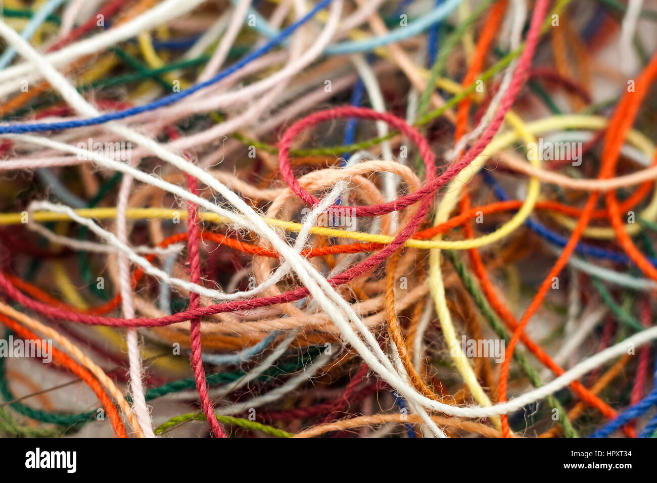 Multi-colored tangled colorful needlecraft silk thread rope. Macro shot. Abstract colors background - Stock Image