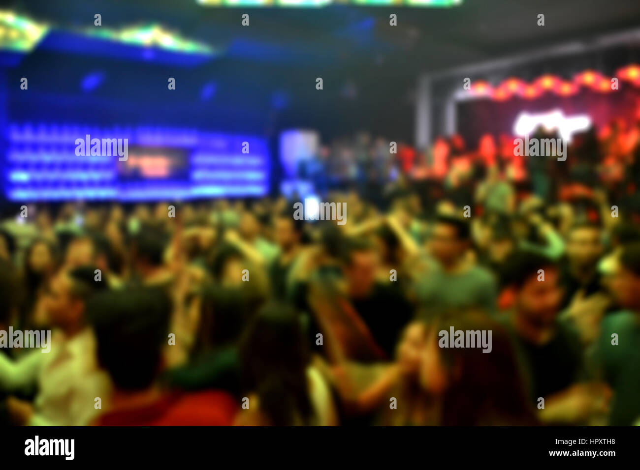 Blurred background of a crowd in an indoor party - Stock Image