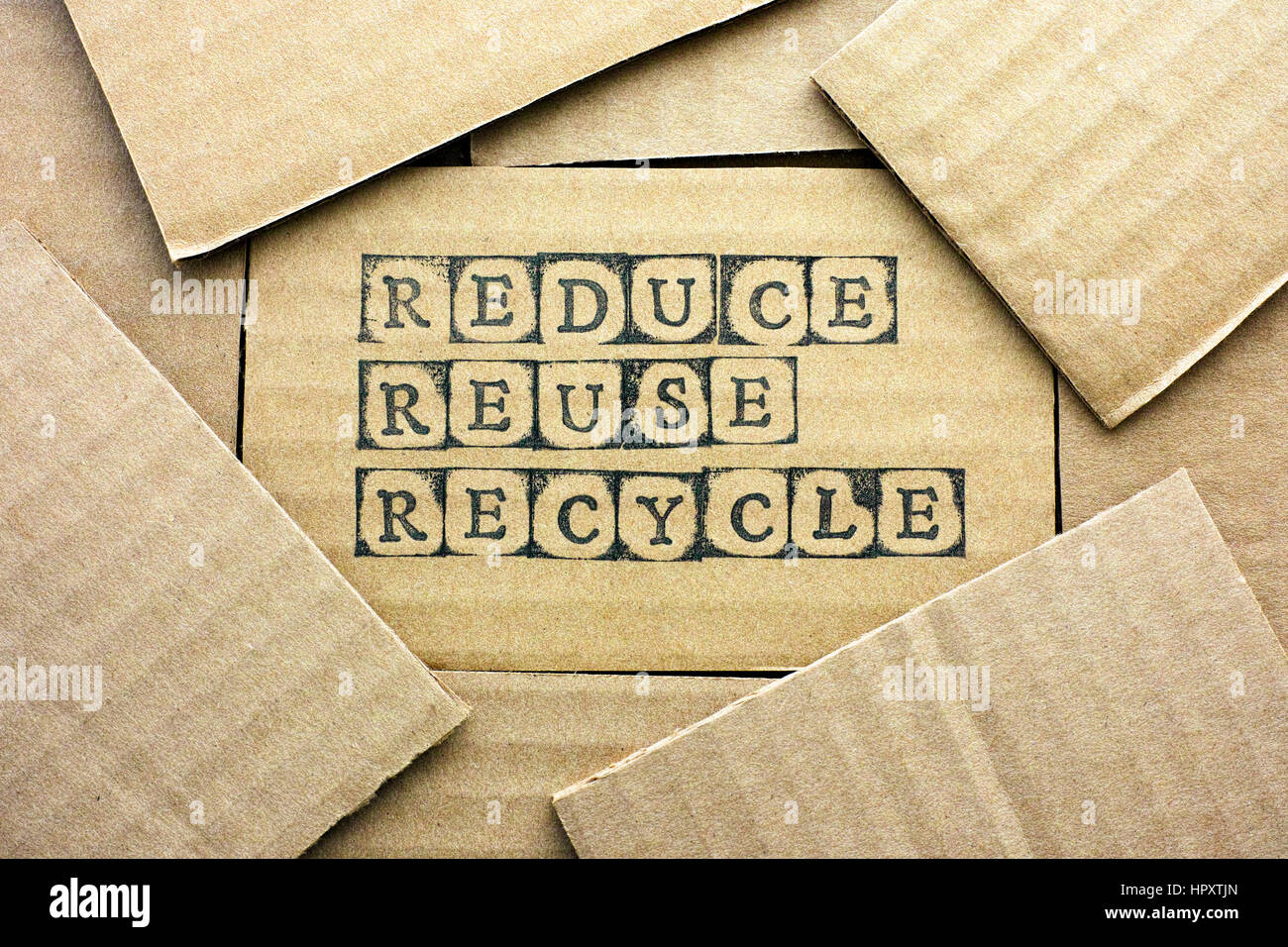 Cardboard card with words Reduce Reuse Recycle made by black alphabet stamps with piece of cardboard. - Stock Image