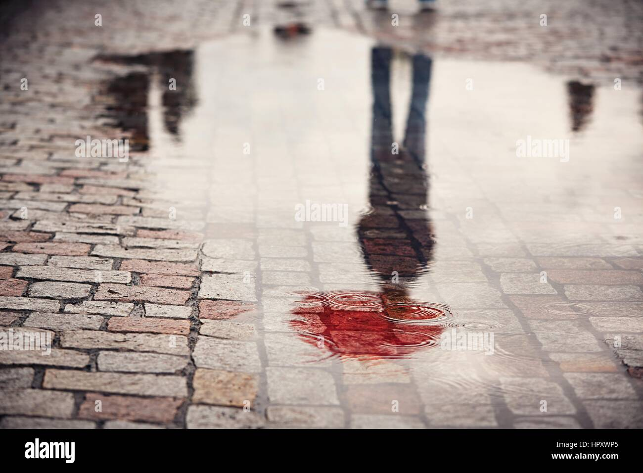 Rainy day. Reflection of young man with red umbrella in puddle on the city street during rain. - Stock Image