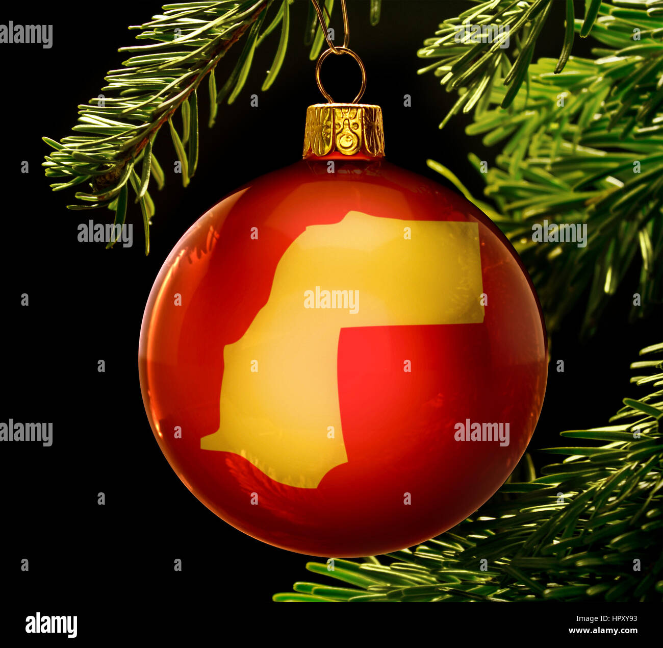 A red bauble with the golden shape of  Western Sahara hanging on a christmas tree isolated on black.(series) - Stock Image