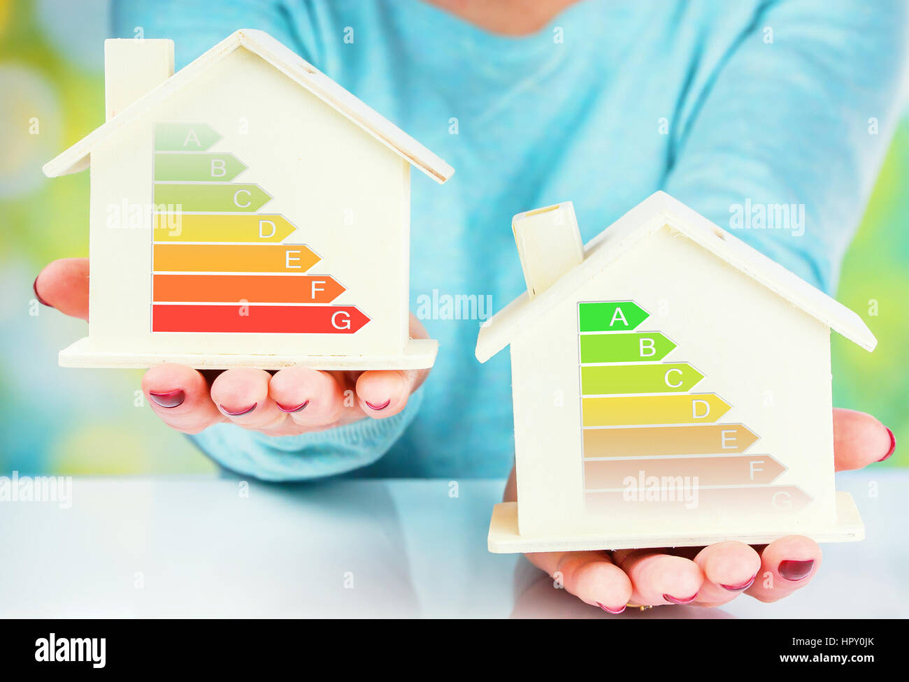 concept comparison between normal house and low consumption house with energy efficiency rating - Stock Image