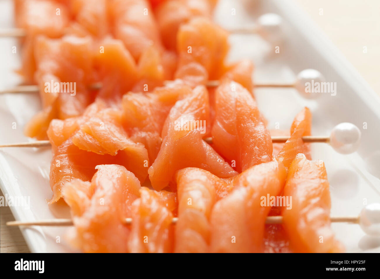 Smoked salmon on cocktail picks with a pearl as a festive snack - Stock Image