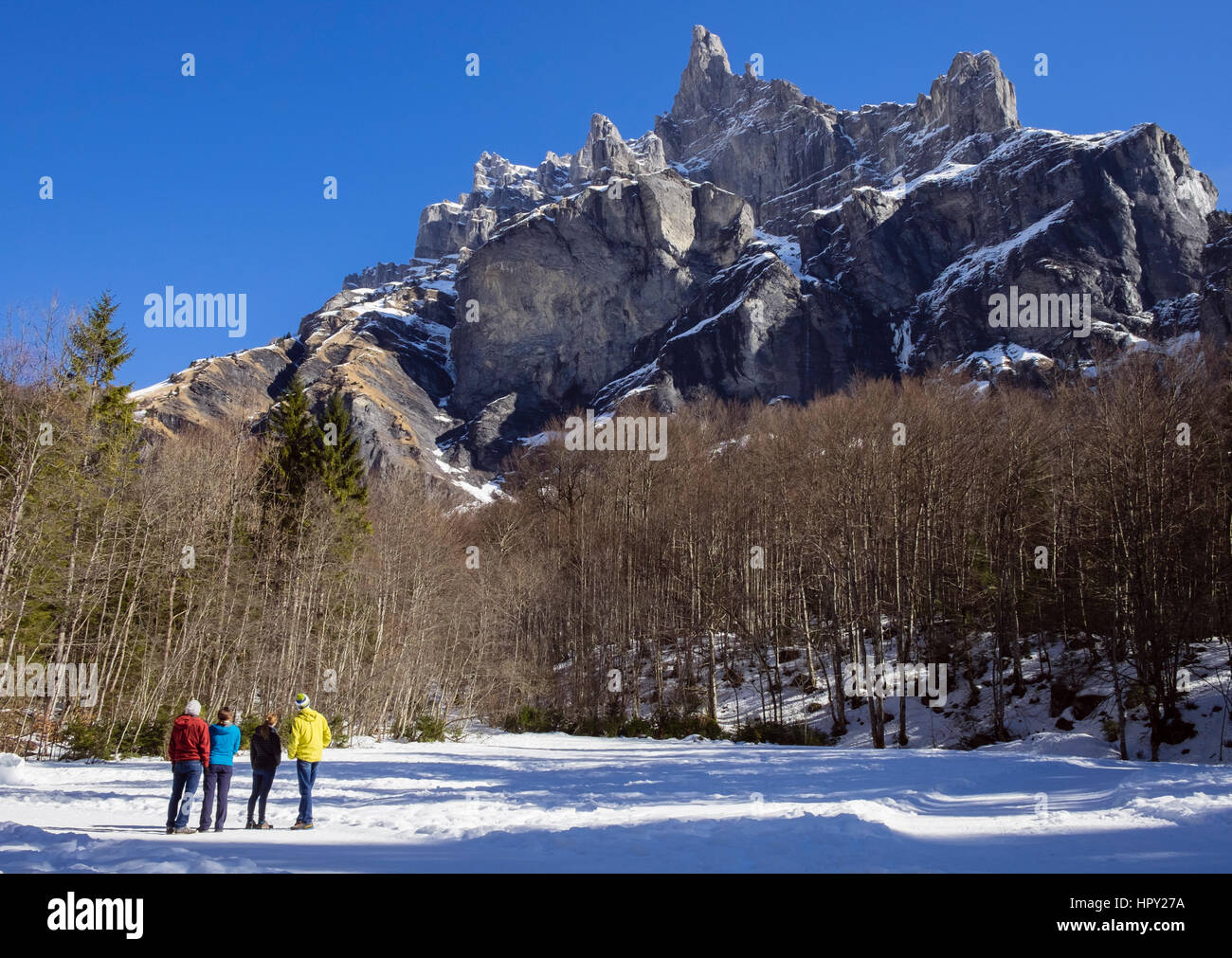 Walkers in Reserve Naturelle de Sixt Fer A Cheval looking up at Pic de Tenneverge mountain in Le massif du Giffre - Stock Image