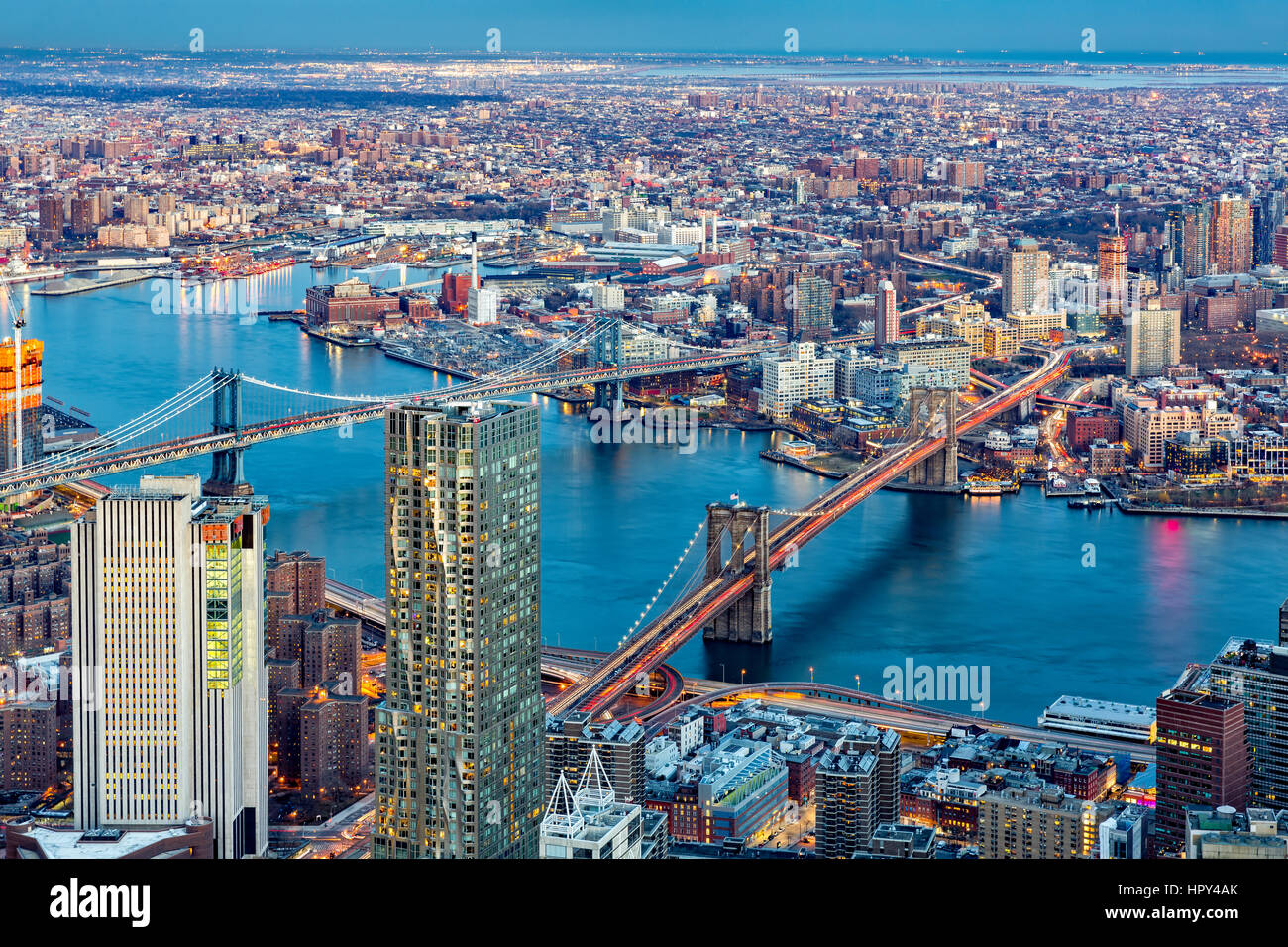 Brooklyn and Manhattan bridges span East River at dusk, between Manhattan island and Brooklyn borough - Stock Image
