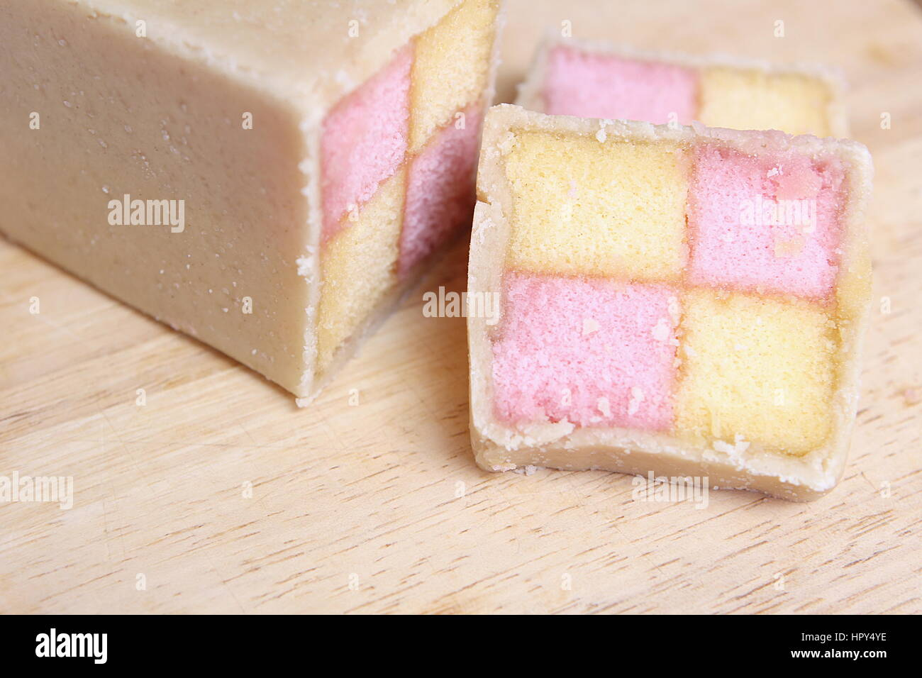 Freshly cut Battenberg Cake with pink and yellow sponge covered in marzipan - Stock Image