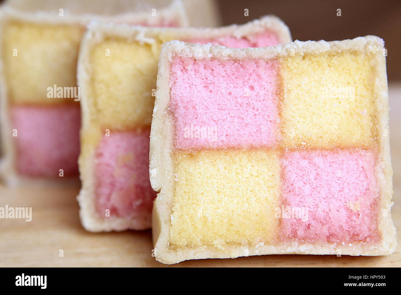 Freshly cut Battenberg Cake slices with pink and yellow sponge covered in marzipan - Stock Image