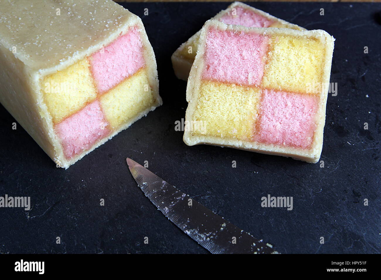 Freshly cut Battenberg Cake on dark slate background with knife. Pink and yellow sponge covered in marzipan - Stock Image