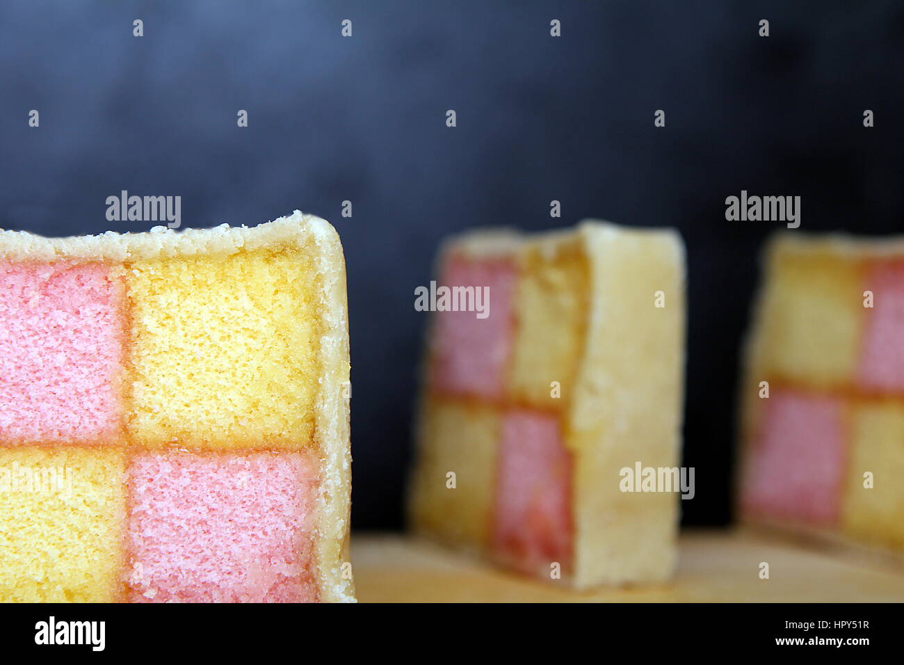 Freshly cut Battenberg Cake slices on wooden board with dark background. Pink and yellow sponge covered in marzipan - Stock Image