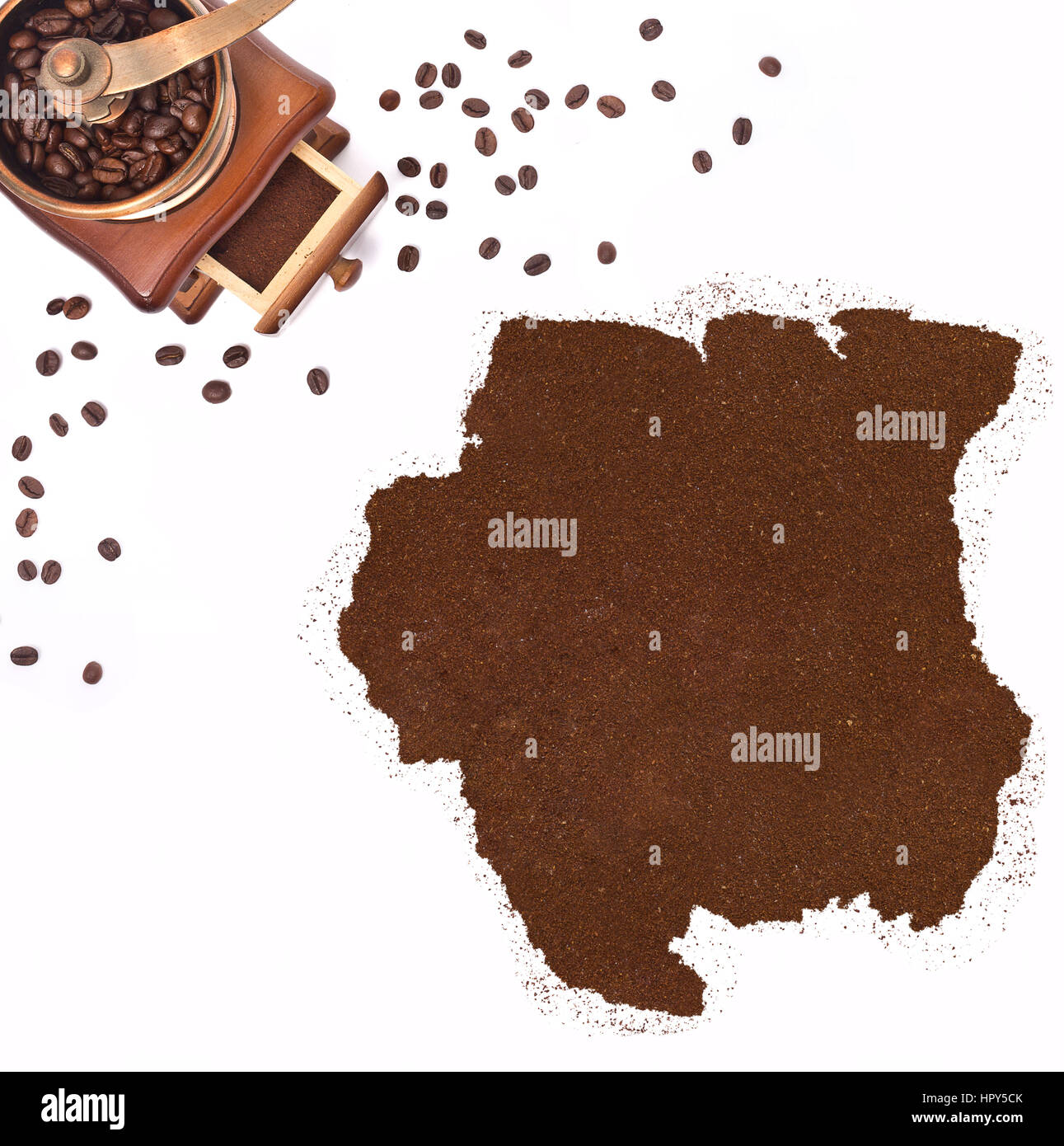 Coffee powder in the shape of Suriname and a decorative coffee mill.(series) - Stock Image