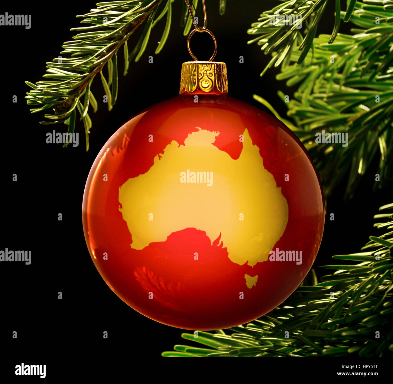 A Red Bauble With The Golden Shape Of Australia Hanging On A Stock