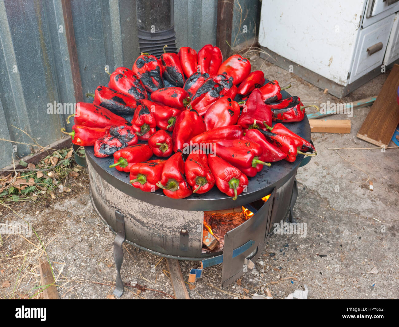 Red peppers roasting on a wood-fired stove in preparation for making ajvar, a traditional Macedonian dish. - Stock Image