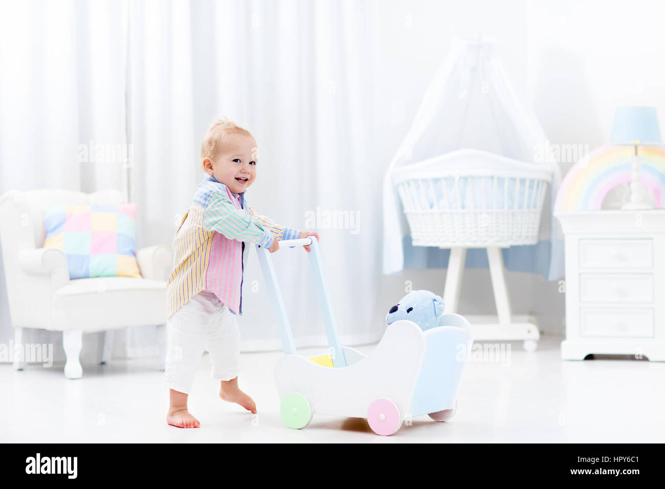 Baby Boy Learning To Walk With Wooden Push Walker In White Bedroom
