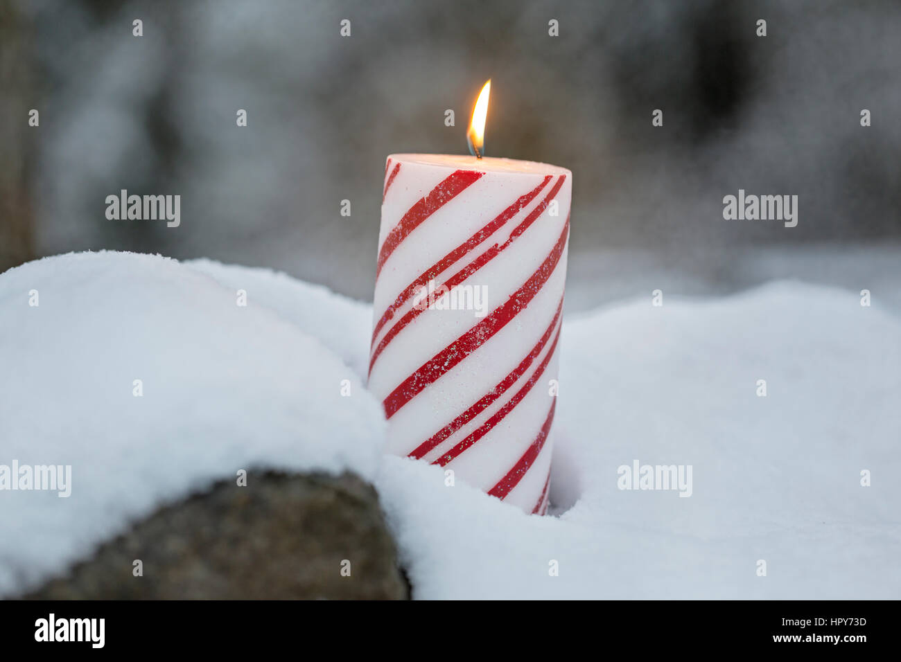 Candle glowing outdoors in snow Stock Photo